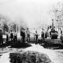 Image of Paving Main Street - Paving Main Street, Mount Airy.  A number of men, some with shovels and other hand tools, with a large roller in the background.