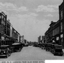 """Image of Main Street, Mount Airy. - Main Street, Mount Airy, looking south from Oak Street, in the 1920s to 1930s.  Note at bottom of picture adds, """"Looking from Blue Ridge Hotel.""""  Several sutomobiles are parked along the street."""