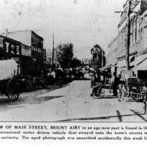 """Image of Main Street, Mount Airy - Main Street, Mount Airy, looking north from Virginia Street, early 1900s.  Information at the bottom of the picture says it was """"unearthed accidentally ...from The NEWS files.""""  Covered wagons can be seen along the street."""
