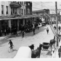 Image of Main Street Mount Airy - Mount Airy Main Street, looking north.  Banner Building on left.  On the street are a covered wagon, horse and buggy, automobile, boy riding a bicycle, several people.