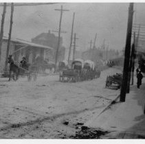 "Image of Mount Airy Main Street - Mount Airy, Main Street looking north, around turn of century.  Note of back of picture reads, ""About where Robbies' is.""  In the street are covered wagons, horse and buggy."