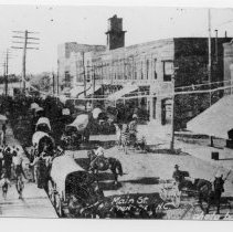"""Image of Main Street, Mount Airy - Mount Airy, Main Street looking north from Franklin Street.  Note on back of picture says, """"Town clock installed 1892.""""  In the street are covered wagons, horse and wagons, rider on horseback, children and adults on sidewalk."""