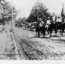Image of Daughters of Confederacy Parade - Daughters of Confederacy Parade for Civil War Veterans, Main Street, Mount Airy, about 1910.  There are several people on horseback, horse-drawn wagons and carriages following, and a few people walking along the side of the street.