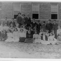 Image of Graduating Class - Mount Airy High School, first graduating class, then at Rockford Street School.  Girls are seated on ground outside building, boys are standing behind them.