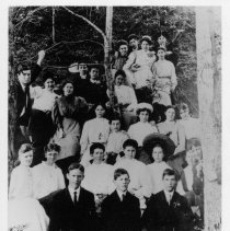 Image of Mount Airy High School Class 1905-1906 - Mount Airy High School Class, 1905-1906 at Mount Airy Mineral Springs. Elizabeth Kelly, teacher. Front row, left to right: ? Nichols, Olin Hanks, Clark Brower.  Second row: Maude McBee, Lizzie Ashley, ?, Clara Foy, Mamie Newton, Nannie Fullon. Third row: Pete McKinney, Miss Kelly, Gertrude Smith, Lena Hatcher, Ora Parker, Minnie Rierson, May Jones, Mattie Webster, Mamie Webster (back of tree). Fourth row: Kate Blackburn, Lizzie McCargo, Sara Banner. Fifth row: Alene Galloway, Frank Carter, Mary Fullon, Frank Penn and ? Creed. Information provided by Bob Watson.