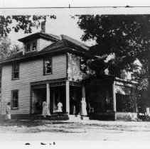Image of Wilcher Banner House - Wilcher Banner House. The dirt basement was originally used for the kitchen. The potato pit was also in the basement. House built before 1888.  Several people are standing on the porch and in the yard.