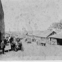 Image of Virginia Street - Virginia Street, Mount Airy.  Horse-drawn wagons are in the street, and several men can be seen standing along the side of the street.