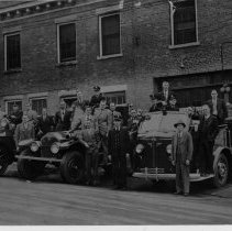 Image of Fire Engines - Mount Airy Fire Engines, with City Hall on Moore Street in background.  A number of men are on the fire engines, and others are standing beside them.