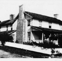 Image of Mitchell's Hotel - Mitchell's Hotel, Fancy Gap, Virginia.  Several people are on the front porch, and a white picket fence surrounds the building.