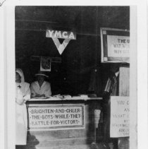 """Image of Mount Airy Red Cross Booth - Mount Airy Red Cross Booth, Surry County Fair, during World War I.  Sign in front of booth reads, """"Brighten And Cheer The Boys While They Battle For Victory.""""  One woman is sitting at the booth, a second is standing beside it."""