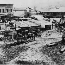 """Image of Downtown Stuart - Stuart, Virginia, picture of downtown at turn of century.  In the background is a large building named """"Clark Bros."""" plus other un-named buildings, and in the foreground are several men, horses, and wagons."""