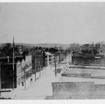 Image of Mount Airy - Mount Airy looking south, with Moore Avenue on left, ca 1890s.  Central Hotel is the white building left center.  A man and a woman can be seen walking along the street.  This is a copy of an original which appears to have been bent on the two left corners.
