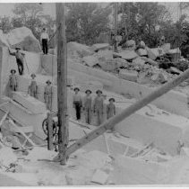 Image of Mount Airy Granite Quarry - Mount Airy Granite Quarry, with nine men standing along a large granite slab, perhaps posing for this picture.