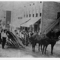 """Image of Farm Equipment - Farm equipment (?) being moved by two horses along North Main Street, Mount Airy. One man, seated, appears to be driving the conveyance, and a number of other men are standing on either side.  The street is unpaved, and a sign under a building awning reads, """"...Irvin."""""""