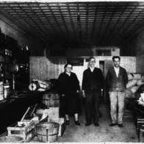 """Image of Grocery Store - Grocery Store on Willow Street, Mount Airy, corner of Franklin and Willow Streets, picture taken in 1930 or 1931.  Standing in the store are Mr. and Mrs. Jesse Booker and son Joseph Samuel """"Sam"""" Booker.  A pot-bellied stove, a barrel, scales,  and a variety of produce can be seen along the sides of the store."""