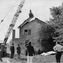 Image of Demolition of Old Jail - Demolition of old jail, Dobson 1976.  Wrecking equipment at left of picture is removing the roof while several people watch.