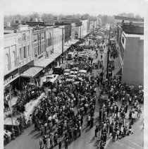 Image of Mount Airy Street Festival - Mount Airy Street Festival, 1968.  A choral group is on a stage at the left, a number of people are standing in the street, and several cars are parked in the middle of the street.