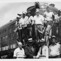 Image of First Diesel to Mount Airy - Train.  First diesel to Mount Airy, 1955.  A number of men are standing on the engine, and several others are posing in front.