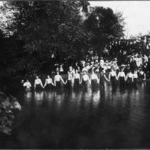 Image of Baptism at Sides Mill - Baptism at Sides Mill,  Haymore Memorial Baptist Church, around 1912.  Several people with hands joined are standing in the water, and a group on onlookers is sitting and standing along the bank.
