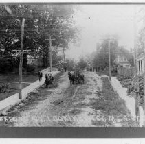 Image of Rockford Street, Mount Airy - Mount Airy.  Rockford Street from South Main Street, probably early 1900s.  A man is walking along the sidewalk, and horses and carriages are in the road.