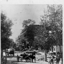 Image of Main Street, Mount Airy - Main Street, Mount Airy, looking south, before Oak Street was cut.  Blue Ridge Hotel is on the right.  The hotel was built in 1891, burned, and was rebuilt in 1892.  Two men are standing near the front of the picture, and two or more horse-drawn wagons are in the road.