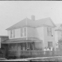 Image of Clem Clevering Home - Clem Clevering home on Rawley Avene, first on left from North Main Street, Mount Airy, since torn down.  The yard is surrounded by a picket fence, and several people, including a man holding a small child, can be seen in the yard.