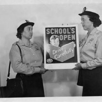 "Image of School Patrol - School patrol.  Georgia Coble and Mrs. Vermont Puckett, both in uniform, holding a sign which reads, ""School's Open Drive Carefully"""