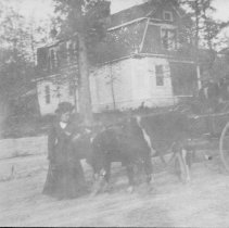 Image of Martha Fisher - Ox team near Mount Airy, with Martha Fisher standing at the head of the team.  Two men are sitting in the wagon, and a house can be seen in the background.