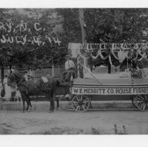 Image of July 4 Parade, 1914 - Mount Airy July 4 parade, 1914, showing  W. E. Merritt Co. House Furnishings float.  Float is pulled by a team of horses decorated with flags, several onlookers can be seen in the background.