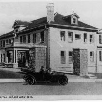 Image of Martin Memorial Hospital - Mount Airy, Martin Memorial Hospital.  A couple in what may be a 1920s touring car are parked in front of the building.