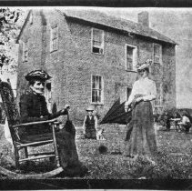 Image of Carter-Burge-Miller House - Carter-Burge-Miller House, Mount Airy vicinity, built 1820-1830., one of the few pre-1900 brick houses in Surry County.  Two ladies and a young boy with dog are in front of the house.  One lady is seated in a rocking chair and the other is standing holding an umbrella.  In the background there is a man with animals.