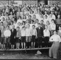 Image of Rockford Street School Student Body - Rockford Street School, Mount Airy, student body.  Children (several barefoot) are standing on wooden bleachers outside the school, with two teachers in long skirts at the side.  None of the students are identified.