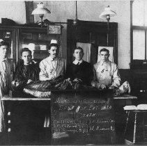 """Image of Autopsy - Five doctors preparing to do an autopsy.  Sign in front of table reads """"Man's Usefullness Does Not End With Death""""  The doctors are identified as E. M. Chitwood,  Va., J. B. Quim, Conn., T. H. Worrell, Va., J. L. Rimsen, N. J., W. T. Rumage, N. J."""