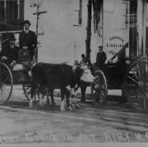 Image of Mount Airy, Main and West Oak Streets - Mount Airy, Main and West Oak Streets, probably early 1900s.  A young boy and two men are in a wagon pulled by oxen, and a man is seated in a second wagon.