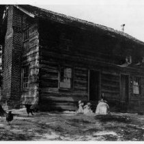 """Image of Matthew Davis House - Home of Matthew Davis on Lovill's Creek, west of Mount Airy Industrial Park. A woman wearing a long dress and head scarf is sitting in front of the log house, and two young children in hats are playing nearby.   Note on back of picture reads: """"C. H. Haynes maternal side.""""  House has been demolished."""