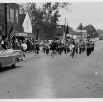 Image of Parade, Pilot Mountain - Parade on East Main Street, Pilot Mountain, looking east.  Lynch Department Store can be seen on the left.  The school band is marching behind a convertible carrying a dignitary.  Several people are standing along the sides of the street.