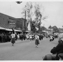 Image of Parade, Pilot Mountain - Parade, East Main Street, Pilot Mountain.  On the north side of the street are T. D. Simmons Store and Pilot Super Market.  The school band is marching behind two flag bearers, and a number of onlookers line the sides of the street.  Clothing would indicate this is a winter event.