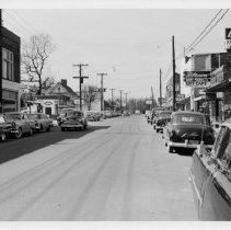 Image of East Main Street, Pilot Mountain - East Main Street, Pilot Mountain, looking west.  1950s cars are parked along the sides of the street.  City Cafe, Midkiff-Carson Hardware, and Surry Drugs can be seen.