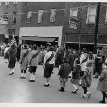Image of Parade, Pilot Mountain - Parade on Main Street, Pilot Mountain, either Veterans Day or Christmas.  Several children, dressed for cold weather, are matching behind a flag-bearer.  A number of bystanders are along the side of the street.