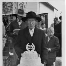 Image of 99th Birthday - Birthday gathering for the 99th birthday of Mr. Scehrist (or Secreast), Pilot Mountain.  He is standing by a three-tiered birthday cake, with several people in the background.