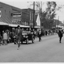 Image of American Legion Parade, Pilot Mountain - American Legion Parade, Pilot Mountain, along north side of East Main Street.  Men dressed as clowns walk beside vintage convertible automobile, and a number on onlookers line the side of the street.  Pilot Super Market and T. D. Simmons Co. stores are in the background.