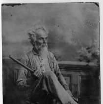 """Image of Mr. Jessie Grubbs - Post card portrait of a Mr. Jessie Grubbs.  Mr. Grubbs, with white hair, a long beard, and dressed in work clothes, is seated in a straight chair and holding a long-handled tool.  The address side of the post card instructs the sender to """"Place One-Cent Stamp Here."""""""