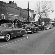 Image of Parade, Pilot Mountain - Parade, Pilot Mountain, Main Street looking east.  1950s model convertibles are carrying dignitaries, there is a float with a lady dressed as Miss Liberty, a Cadillac hearse, and other vehicles.  A number of onlookers are on the sidewalk.