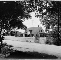 Image of Butler Street, Pilot Mountain - Butler Street, Pilot Mountain.  There are two houses surrounded by picket fences, and two cars can be seen along the street.