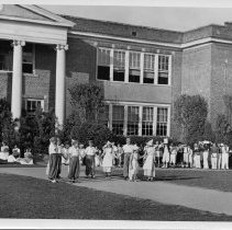 Image of May Day Festivities - May Day Festivities, Pilot Mountain High School, early 1940s.  The May Queen and her court are seated on the front steps, and elementary students dressed as Dutch children are on the front walk.  Other students are standing along the front of the building.