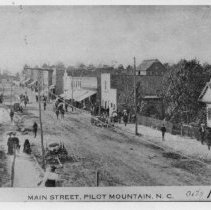 Image of Main Street, Pilot Mountain - East Main Street, Pilot Mountain, looking west, 1905.  Horses and wagons are in the street, several men and women are along the sidewalks.