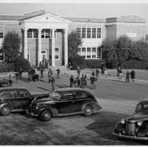 Image of Pilot Mountain High School - Pilot Mountain High School, late 1930s.  A number of students are in the yard, and four 1930s model automobiles are parked on the grounds.