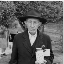 Image of Mr. Sechrist's 99th Birthday - Mr. Sechrist's 99th birthday celebration, Pilot Mountain.  He is wearing a coat and hat, and holding a jar of what appears to be candy.