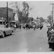 Image of Christmas Parade, Pilot Mountain - Christmas Parade on East Main Street, Pilot Mountain, probably 1950s.  A 1956 or 1957 Chevrolet Convertible is in front of the band.  Several onlookers are standing along both sides of the street.