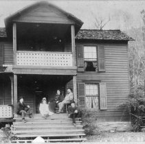 Image of Boyles Family - William Walter Boyles House, Pilot Mountain.  Seated on the porch are William Walter Boyles and wife Flora Stephens Boyles, who was the daughter of James Francis Stephens and Lucinda Boyles Stephens. The children are Claude Boyles and Ethel Boyles (who married Earl Rathmussen), and an unidentified young boy is also with them on the porch.  Picture probably made in early 1900s.